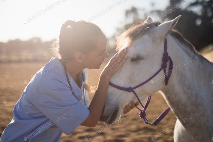 side view of female vet stroking horse