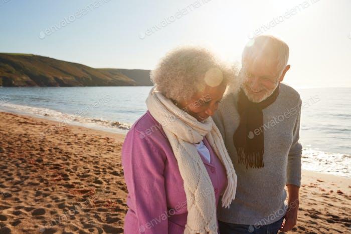 Liebevolle pensionierte Paar Hand halten, wie sie entlang Küste auf Winter Strand Urlaub gehen