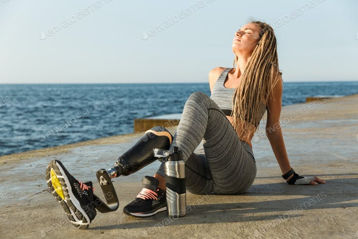 Satisfied disabled athlete woman with prosthetic leg