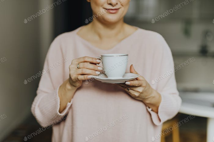 Happy woman enjoying a warm cup of tea for breakfast