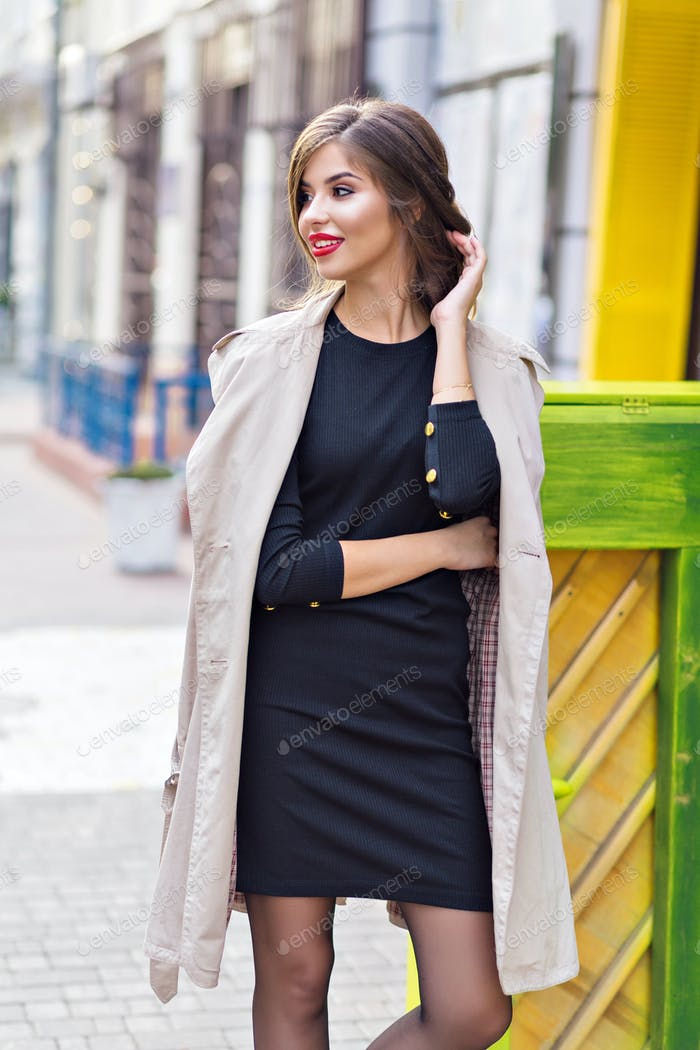Gaceful lady in elegant outfit is happily posing while walking on the street in a good mood.