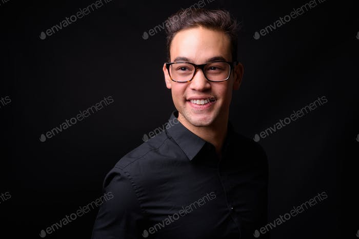 Young handsome multi ethnic businessman against black background