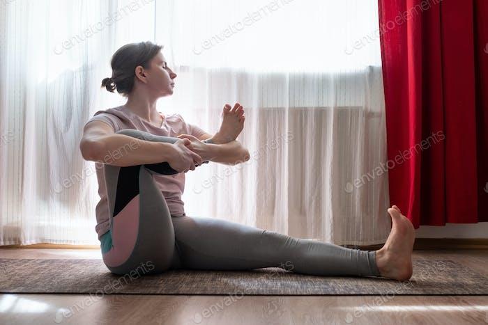Frau im Auge der Nadel Pose im Yoga.
