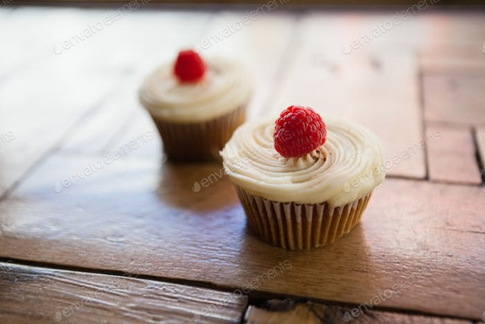 Close up of raspberry cupcakes on wooden table