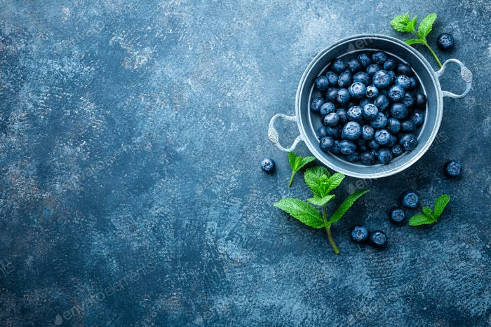 Fresh Blueberries in a bowl on dark background, top view. Juicy wild forest berries, bilberries