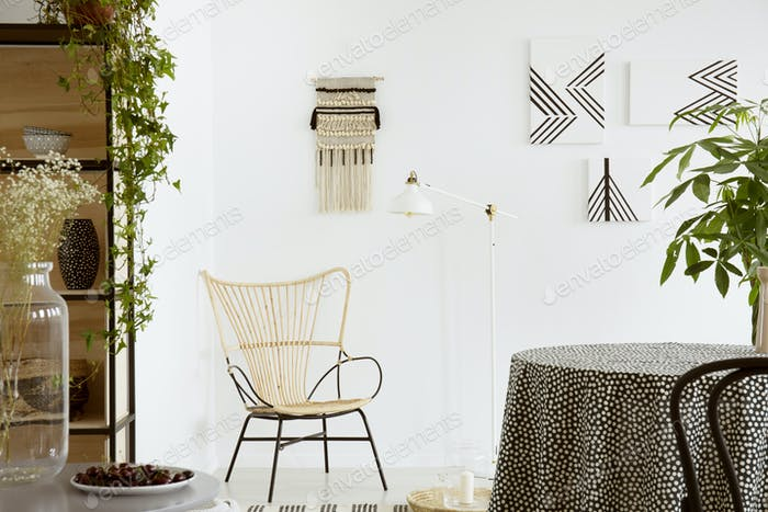Real photo of a garden chair standing against white wall with ma