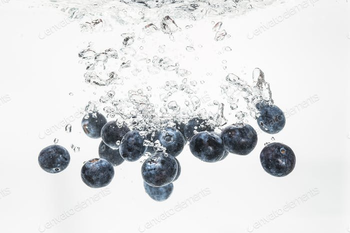 Blueberries sinking underwater with air bubbles isolated on white background