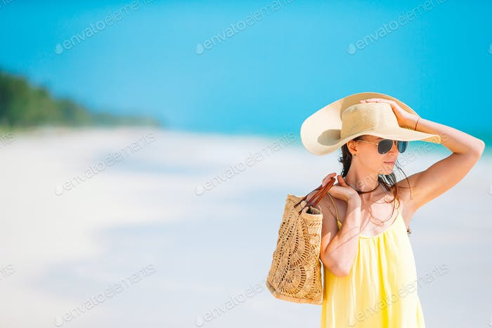 Young beautiful woman having fun on tropical seashore. Happy girl background the blue sky and