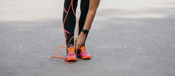 Cardio training and athletics. African american woman with fitness tracker straightens sneakers