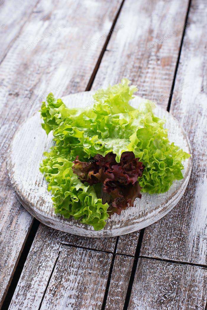 Green fresh lettuce on light wooden board