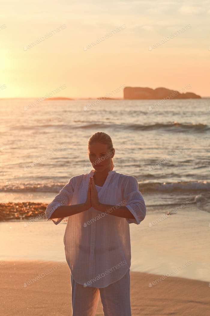 Woman practicing yoga during the sunset