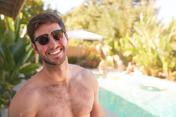 Portrait Of Smiling Bare Chested Man Wearing Sunglasses Outdoors With Friends At Summer Pool Party