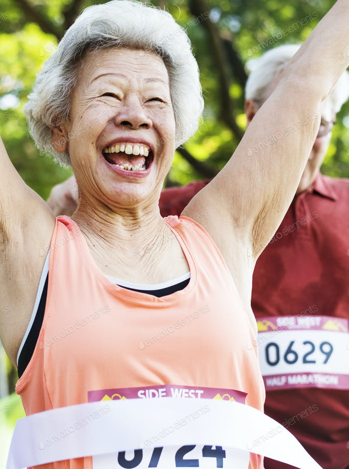 Elderly asian woman reaching the finish line