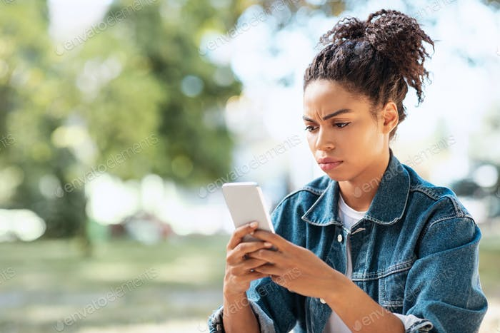 Discontented African American Woman Using Smartphone Reading Negative Message Outdoors