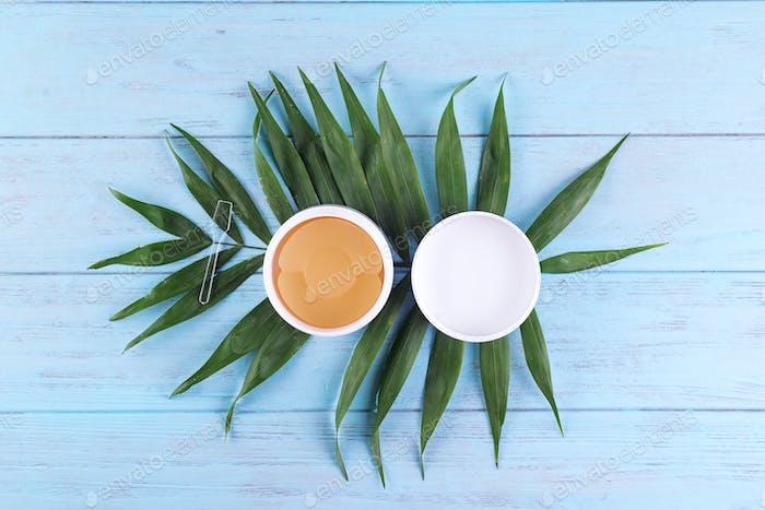 Hydrogel goldene kosmetische Augenklappe in Packung auf Holzhintergrund mit Palmenblättern. Gesichtspflege