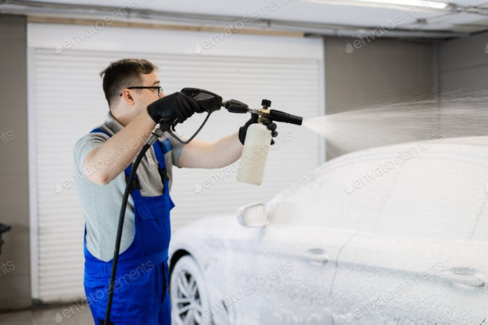 Worker covering automobile with foam at car wash