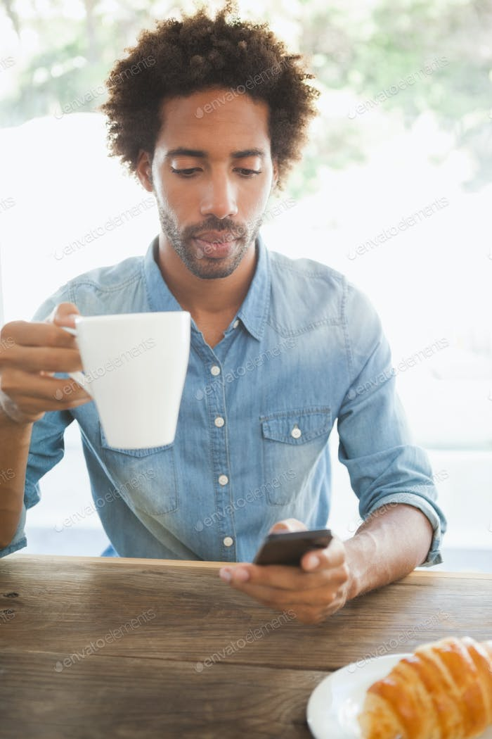 Casual man having coffee while using smartphone at the coffee shop