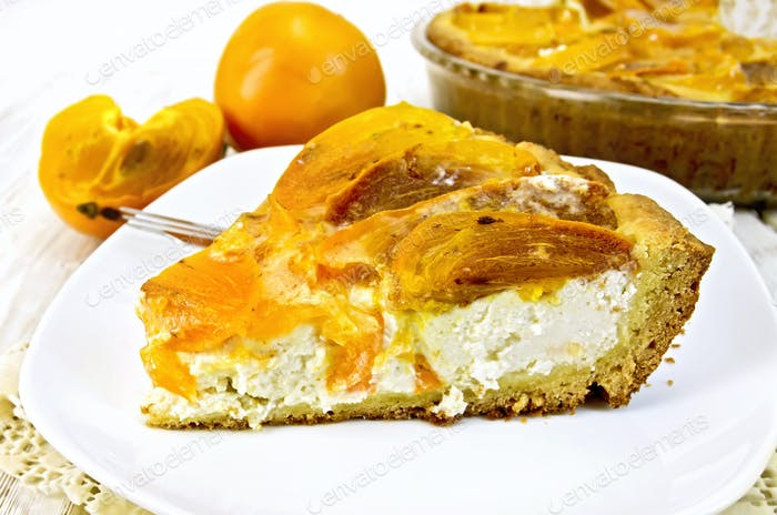 Pie with curd and persimmons in plate on napkin silicone and board