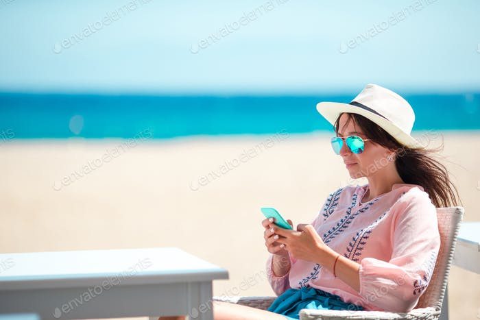 Woman with cellphone outdoors on the beach. Tourist using mobile smartphone