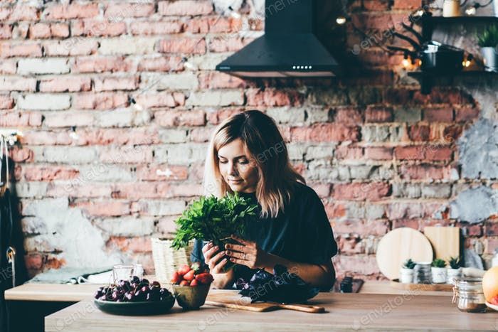 Woman holding greenery at the kitchen.
