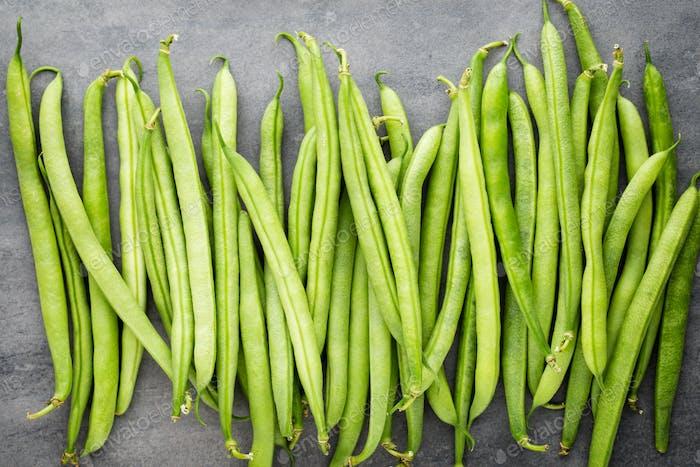 Grüne Bohnen auf einem grauen Hintergrund.