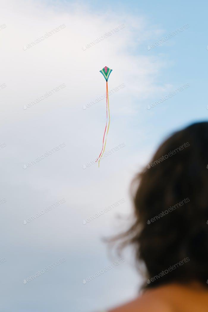 Girl watching kite flight