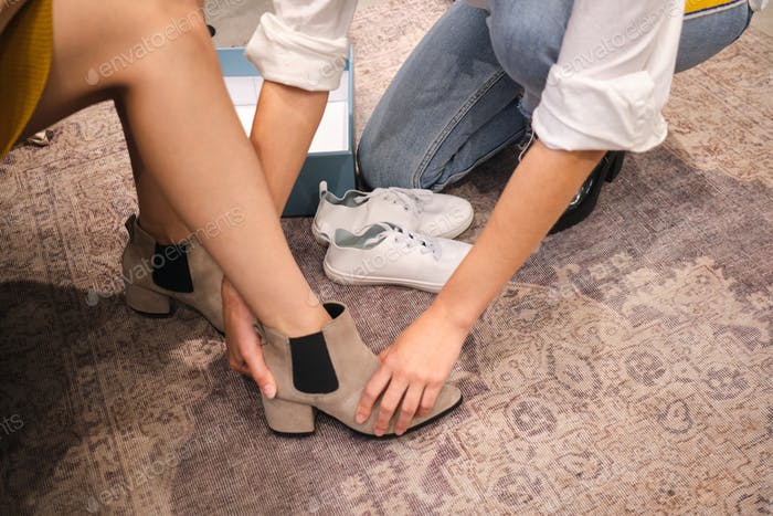 Close up consultant helping trying on casual boots to customer in showroom