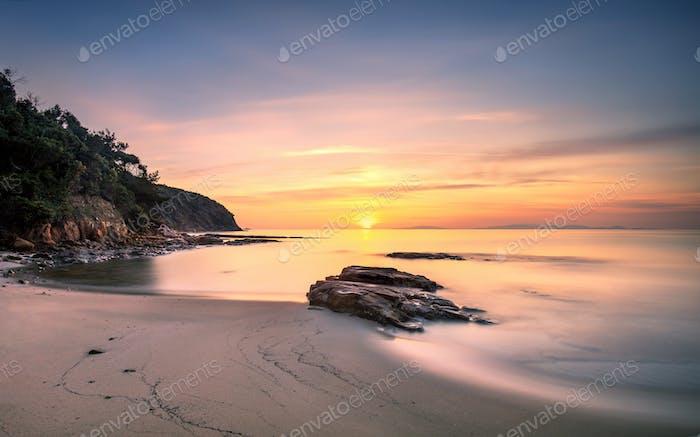 Sunset in Cala Violina bay beach in Maremma, Tuscany. Mediterran