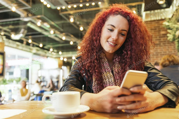 Young woman sitting in trendy cafe writing with her mobile phone.