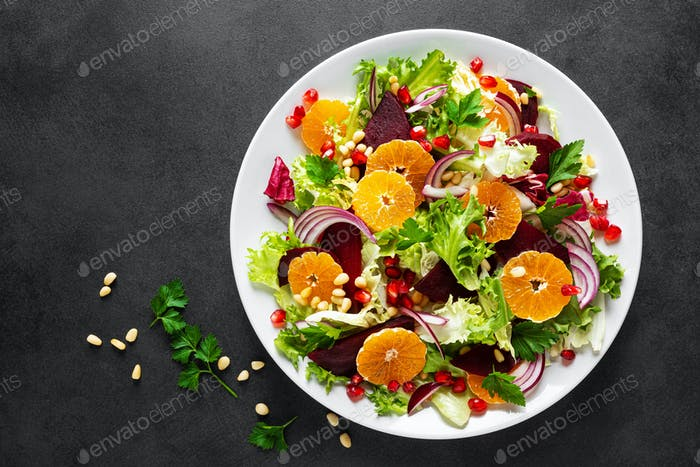 Christmas salad with boiled beet, red onion, tangerines, pomegranate, parsley, pine nuts and lettuce