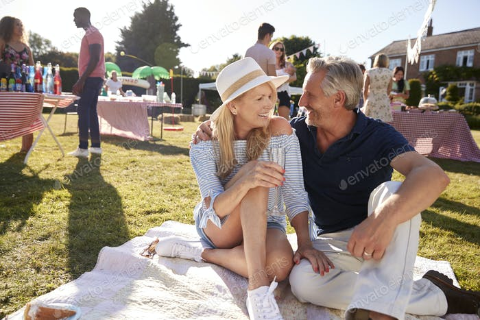 Mature Couple Sitting On Rug At Summer Garden Fete