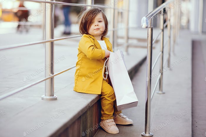 Cute little girl with shopping bag in a city