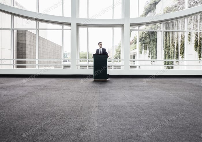 Businessman at a podium with no one to talk to.