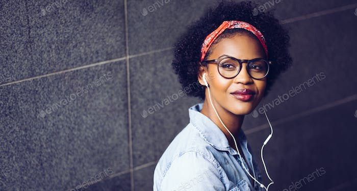 Stylish young woman listening to music on earphones