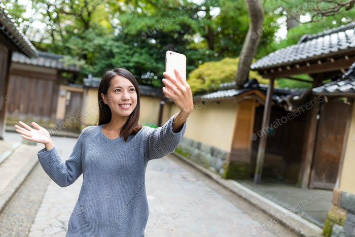 Woman taking selfie photo with mobile phone in kanazawa