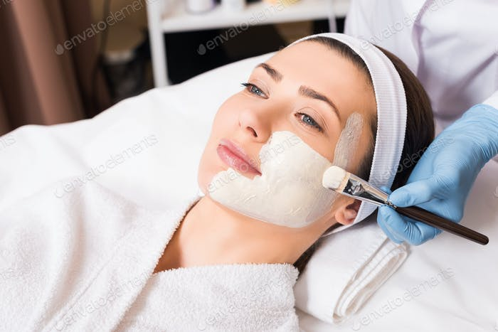 beautician applying cosmetic mask on part woman face with cosmetic brush at beauty salon