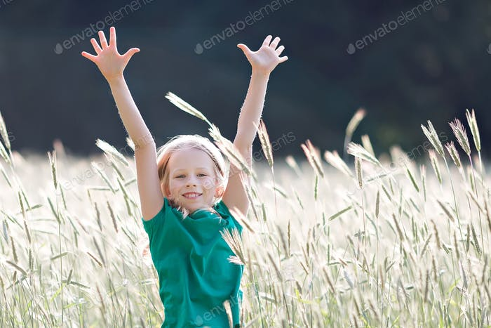 Girl on the field of ripe grain