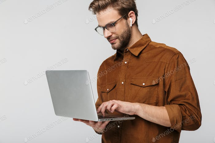 Portrait of handsome young man using laptop and earphone
