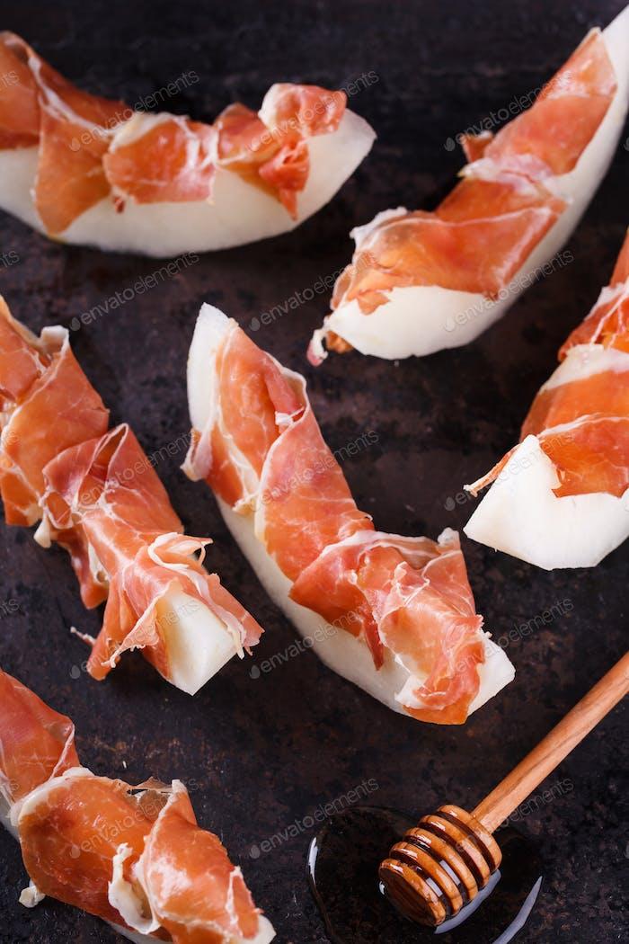 Melone mit Serrano-Schinken, in Scheiben geschnitten mit Honig