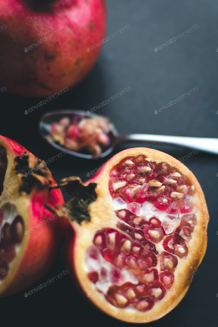 Fresh cut pomegranate on a wooden background