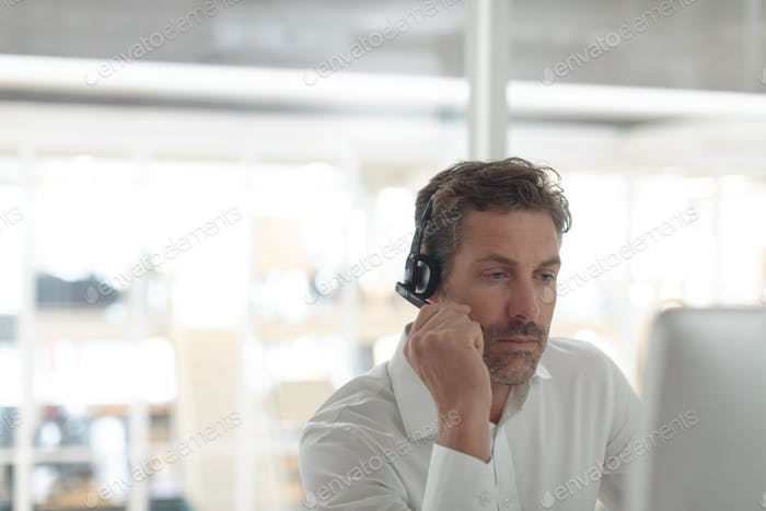 Caucasian male customer service executive talking on headset at desk