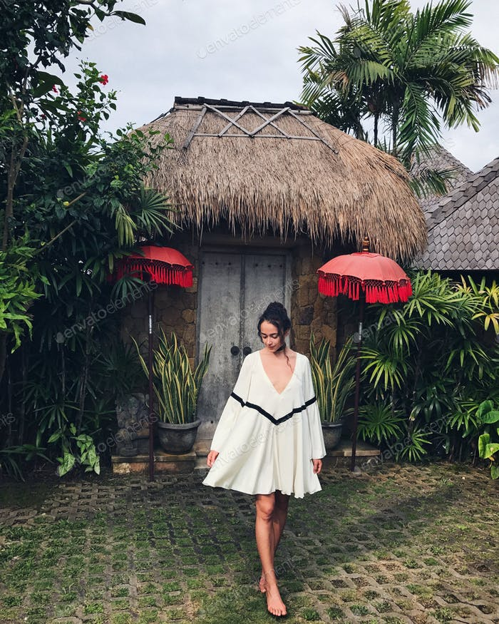 Young woman in white tunic in Ubud village with traditional balinese architecture. Style of Bali