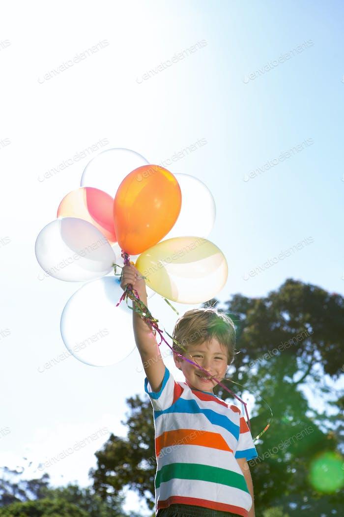 Glücklicher kleiner Junge hält Ballons an einem sonnigen Tag
