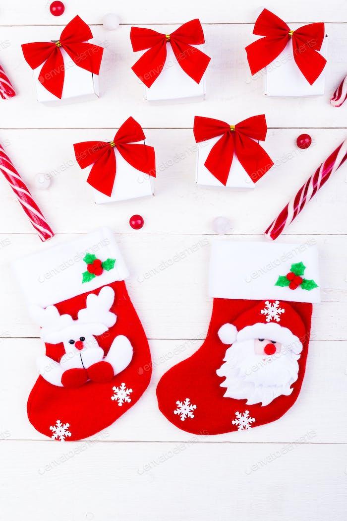 Weihnachtssocken und Geschenke, weiße kleine Boxen mit roter Schleife und Bonbons auf weißem Holzhintergrund