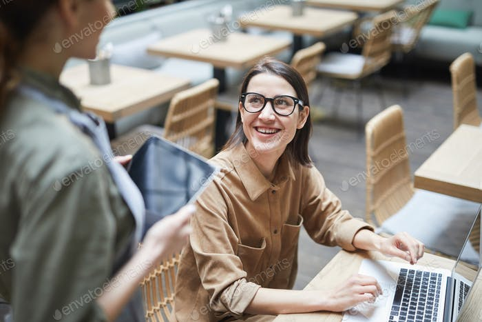Smiling Businesswoman Ordering Coffee in Cafe