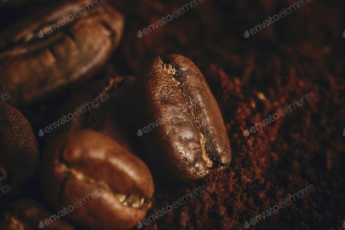 Kaffeebohnen aus der Nähe auf gemahlenen Kaffeehaufen