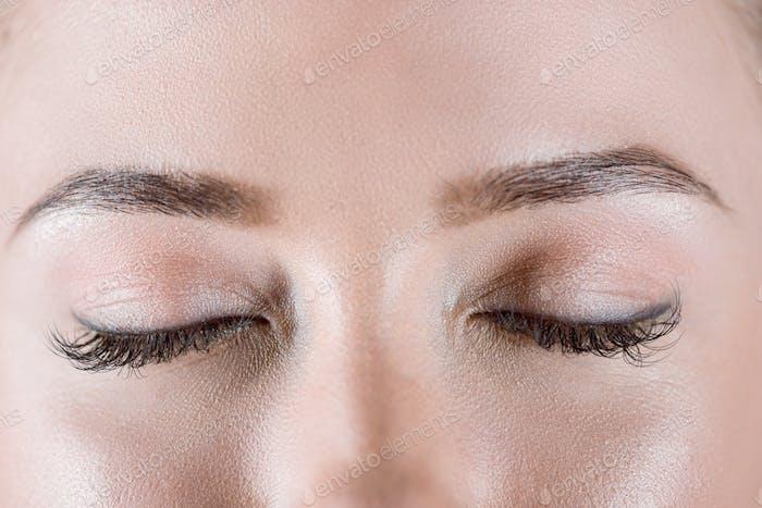 Close-up view of closed female eyes with long eyelashes