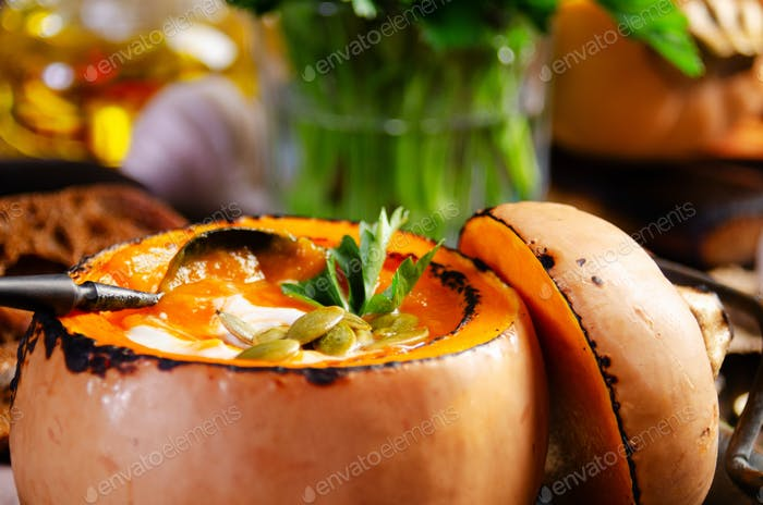 Homemade rustic pumpkin soup with seeds in pumpkin shell on kitchen table with bread aside