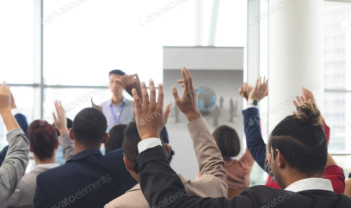 Diverse business people raising hands while an Asian businessman is speaking at business seminar