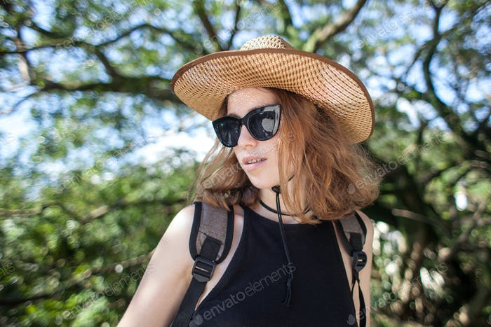young female traveler in hat and sunglasses at sunny summer day on mountains and sea background